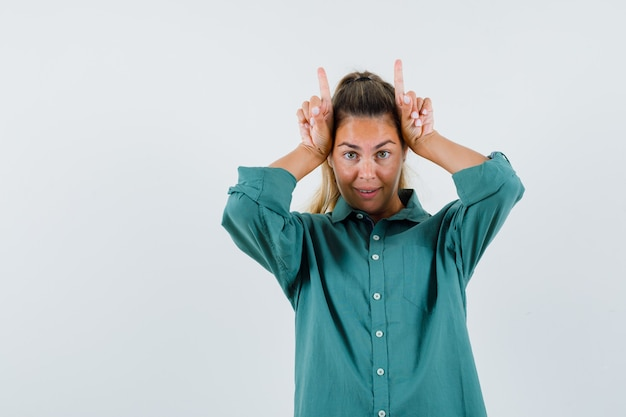 Young woman holding fingers over head as bull horns in green blouse and looking cute