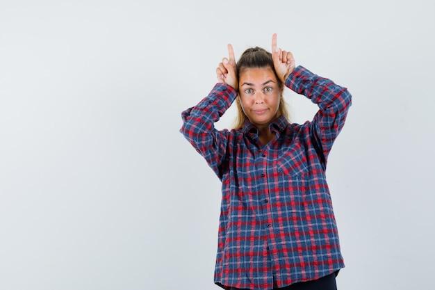 Молодая женщина держит пальцы над головой в виде бычьих рогов в клетчатой рубашке и выглядит удивленно