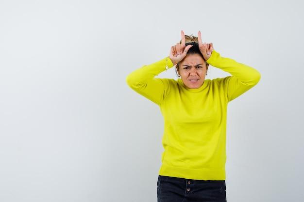 Молодая женщина держит пальцы над головой в виде бычьих рогов в желтом свитере и черных штанах и выглядит сердитой