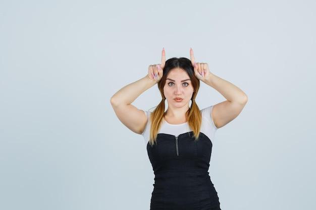 角として頭の上に指を保持している若い女性