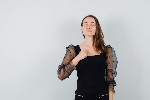 Giovane donna che tiene il pugno sul petto in camicetta nera e sembra altezzosa