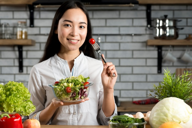 Young woman holding fork with tomato and healthy salad standing in kitchen