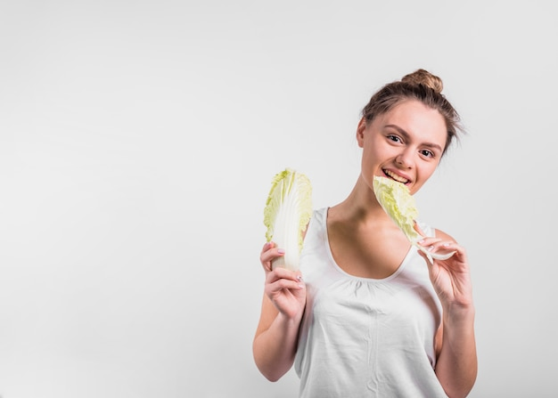 Young woman holding fresh cabbage