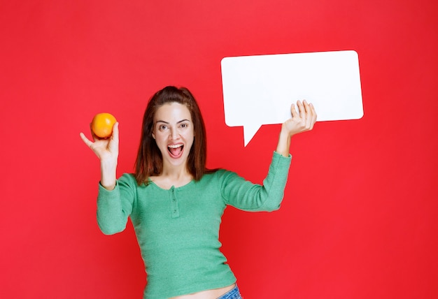 Young woman holding a fresh orange and a rectangle info board