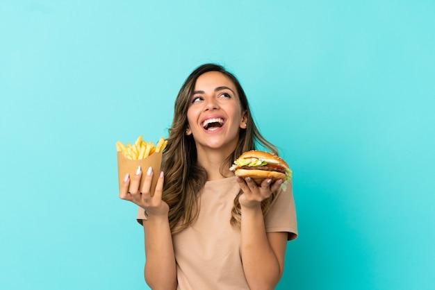 Молодая женщина, держащая жареные чипсы и гамбургер на изолированном фоне