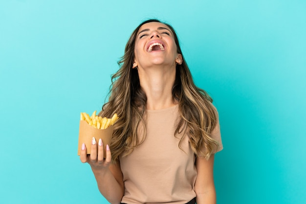 Young woman holding fried chips over isolated background laughing