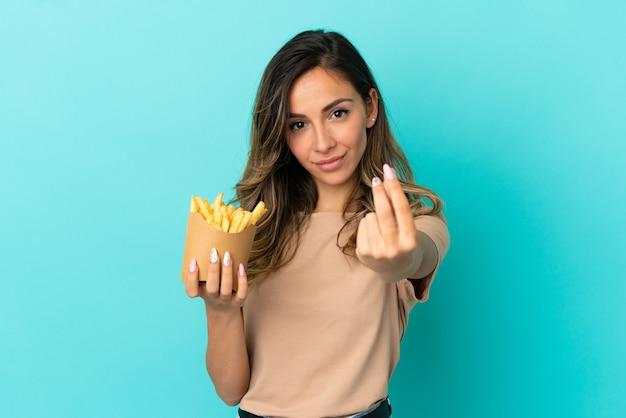 Молодая женщина, держащая жареные чипсы на изолированном фоне, делая денежный жест