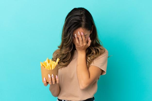 Молодая женщина, держащая жареные чипсы на изолированном фоне с усталым и больным выражением лица