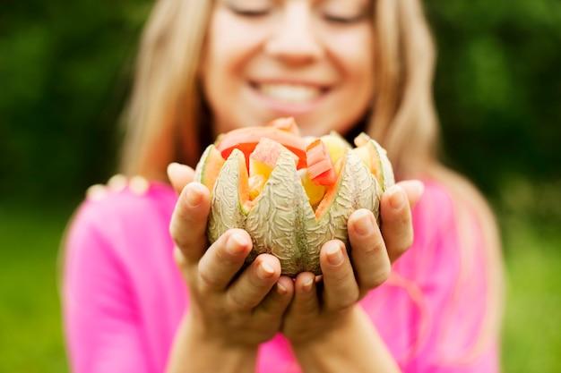 Молодая женщина, держащая фрукты и овощи