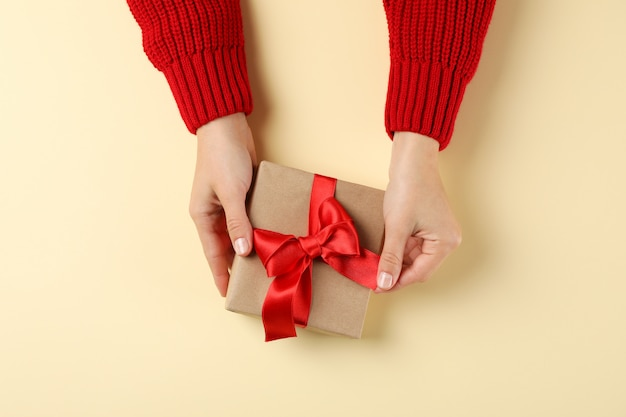Young woman holding gift box on color background, space for text