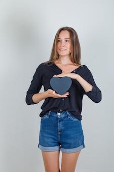 黒のシャツ、ジーンズのショートパンツでギフトボックスを保持している若い女性