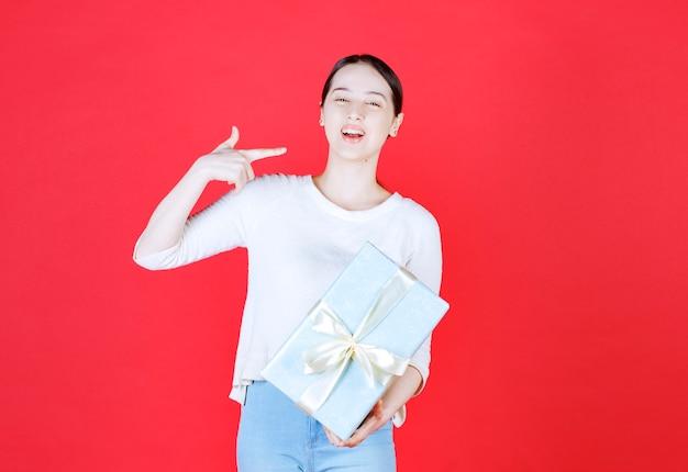 Giovane donna che tiene in mano una scatola regalo e ride
