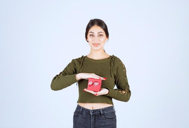 Contenitore di regalo della tenuta della giovane donna e che esamina macchina fotografica su fondo bianco.