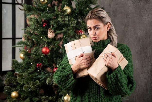 Contenitore di regalo della holding della giovane donna vicino a un albero di natale