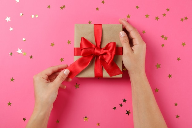 Young woman holding gift box on pink background, space for text