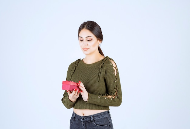 Contenitore di regalo della tenuta della giovane donna su fondo bianco.