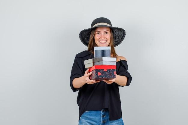 Giovane donna che tiene i contenitori di regalo in camicia, pantaloncini, cappello e che sembra allegro. vista frontale.