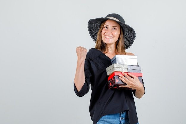 Giovane donna che tiene i contenitori di regalo mentre mostra il segno del vincitore in camicia, pantaloncini, cappello e sembra allegro. vista frontale.