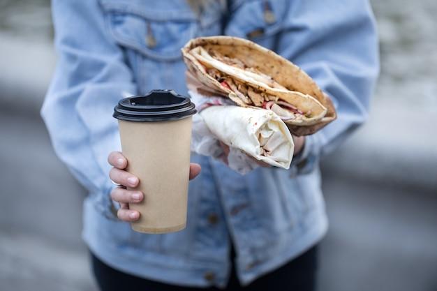 Una giovane donna con in mano un bicchiere di caffè e fast food