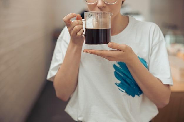 芳香族コーヒーのガラスカップを保持している若い女性