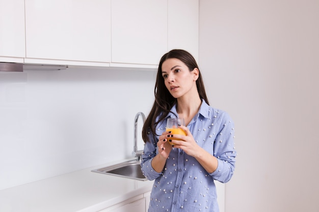 Young woman holding glass of juice standing in the kitchen