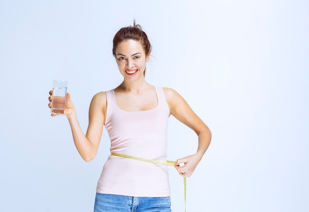 Young woman holding a glass of pure water and measuring her waist size