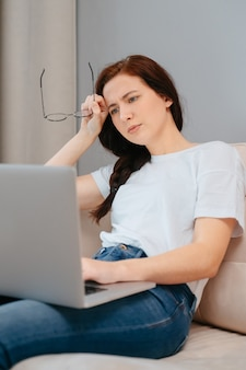 Young woman holding glasses in her hands reads messages on a laptop while sitting at home on the couch