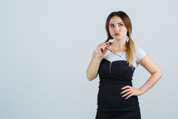 Giovane donna che tiene gli occhiali in bocca mentre tiene la mano sull'anca