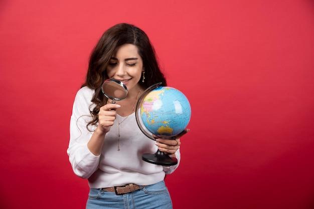 地球儀と虫眼鏡を持つ若い女性。高品質の写真