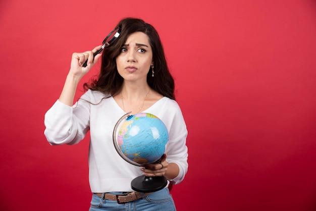 地球儀と虫眼鏡を持ちながら考えている若い女性。高品質の写真