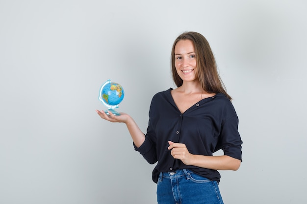 Молодая женщина держит глобус в черной рубашке, джинсовых шортах и выглядит позитивно