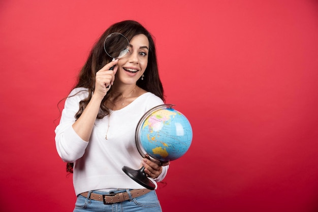 Giovane donna che tiene il globo e lo guarda con la lente d'ingrandimento. foto di alta qualità