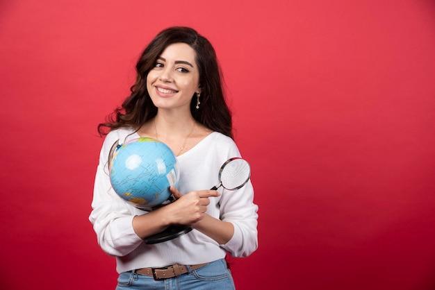 Globo e lente d'ingrandimento della tenuta della giovane donna. foto di alta qualità