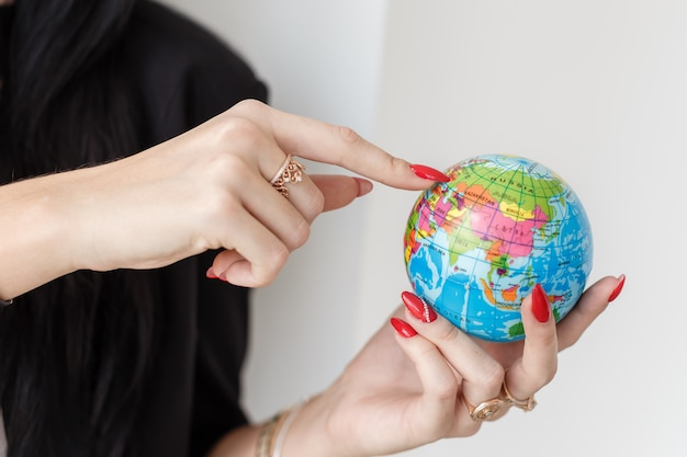 Young woman holding a globe of the planet earth, showing by finger to ukraine