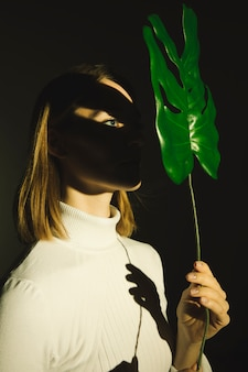 Young woman holding green leaf at face