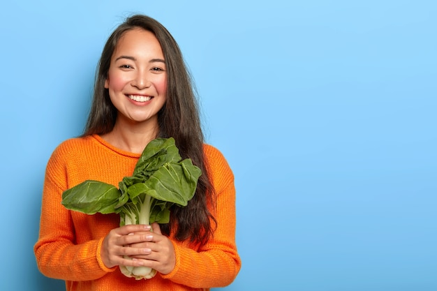 緑の葉を保持している若い女性