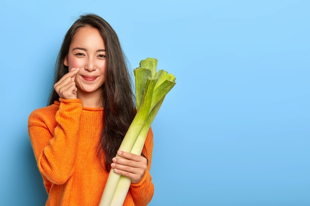 Young woman holding green leeks