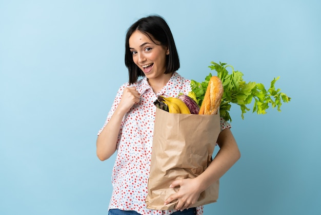 Young woman holding a grocery shopping bag celebrating a victory