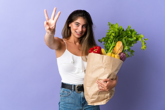 Young woman holding a grocery shopping bag happy and counting three with fingers