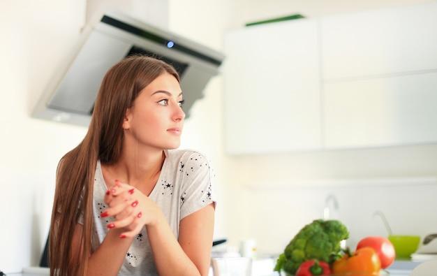 부엌에 야채가 서 있는 식료품 쇼핑백을 들고 있는 젊은 여성