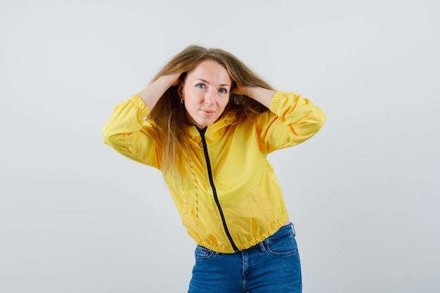 Young woman holding hair and posing at camera in yellow bomber jacket and blue jean and looking attractive. front view.