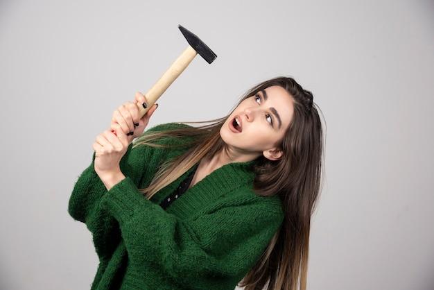 Giovane donna che tiene il martello in mano su uno sfondo grigio.