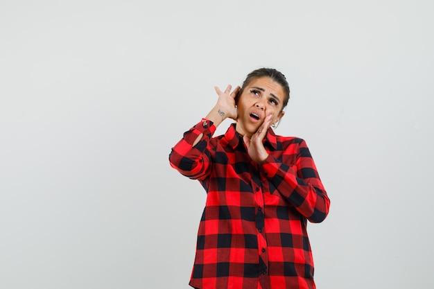 チェックシャツを着て耳の後ろで手をつないで好奇心旺盛な若い女性。正面図。