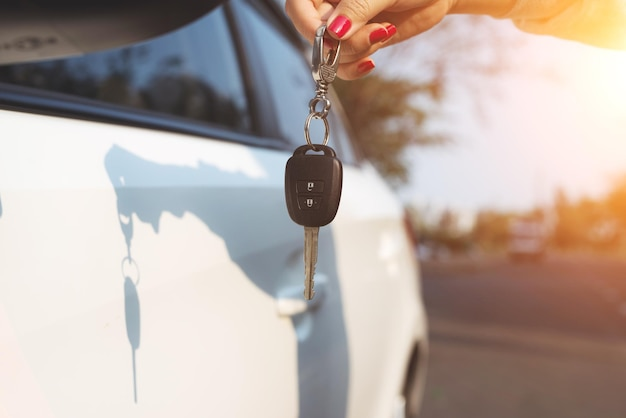 Young woman holding in a hand car keys.