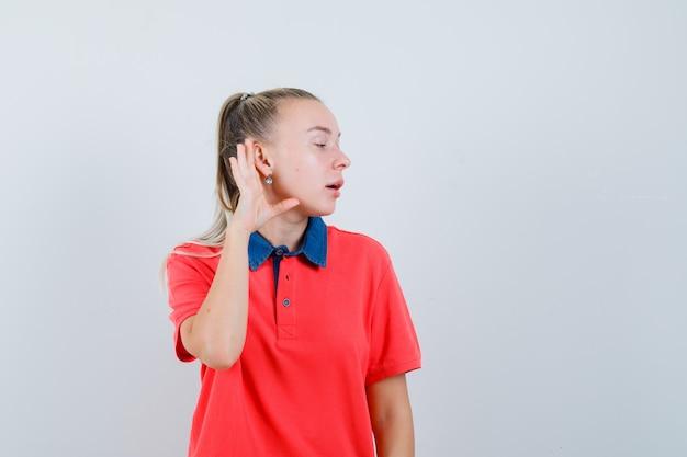 Giovane donna che tiene la mano dietro l'orecchio in maglietta e guardando curioso