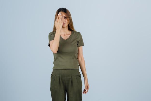 Giovane donna che tiene la mano sull'occhio in maglietta, pantaloni e sembra ottimista. vista frontale.