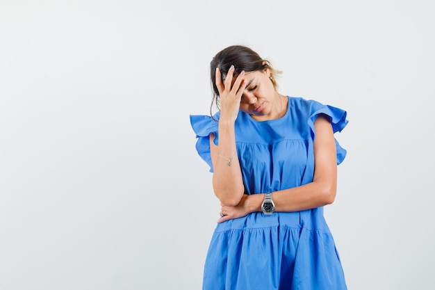 Young woman holding hand on forehead in blue dress and looking exhausted