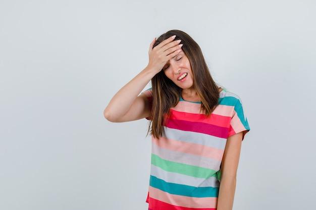 Giovane donna che tiene la mano sulla fronte in maglietta e guardando dispiaciuto, vista frontale.