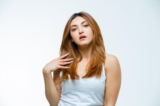 Giovane donna che tiene la mano sui capelli