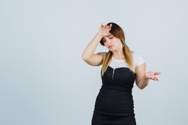 Giovane donna che tiene la mano sulla testa e sembra infastidita